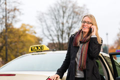 Young woman in front of taxi with phone Stock Photography