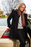 Young woman in front of taxi with phone Royalty Free Stock Photo