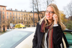 Young woman in front of taxi with phone Stock Image