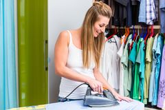 Young woman in front of wardrobe ironing the laundry Stock Images