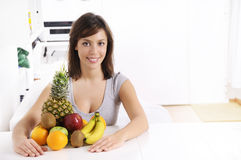 Young woman with fruit. Smiling and looking in camera Royalty Free Stock Images