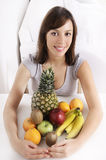 Young woman with fruit. Smiling and looking in camera Stock Image