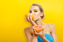 Young woman with fruits on bright orange background Stock Photo