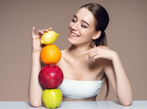 Young woman with fruits mix, healthy life concept . Photo of attractive girl indicates on fruit pyramid /portrait of girl with fruits mix on the table over stock photo