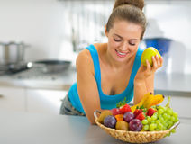 Young woman with fruits plate eating apple Stock Image