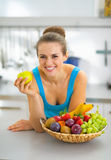 Young woman with fruits plate eating apple Stock Images