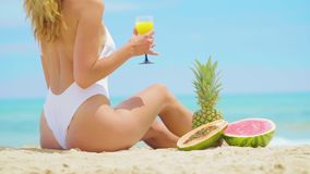Young Woman with fruits Relaxing on the Beach. Young Woman with fruits Relaxing on the Beach stock video footage