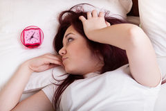 Young woman frustrated of alarm clock Stock Photos