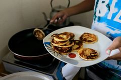 Young woman frying pancakes for breakfast at home in kitchen Stock Photography