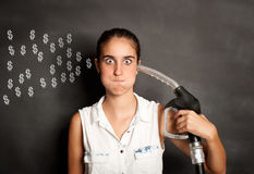 Young woman with a fuel pump nozzle. Young woman shooting herself with a fuel pump nozzle stock images