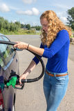 Young woman fueling car tank with gasoline. Young caucasian woman filling up tank of car with benzine Royalty Free Stock Images