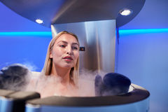 Young woman in a full body cryotherapy cabinet. At cosmetology clinic. She is receiving skin treatment using cold nitrogen vapors Royalty Free Stock Image