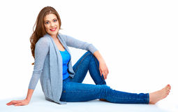 Young woman full body portrait. Beautiful smiling girl. Sitting on white floor Stock Photos