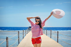 Young woman full of energy on a pontoon in front of the sea on a sunny day Stock Image