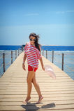 Young woman full of energy on a pontoon in front of the sea on a sunny day Royalty Free Stock Image