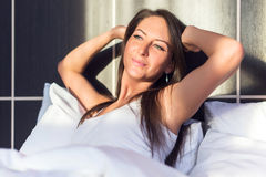 Young woman full of energy, waking up, smilling, stretching in bed stock photo