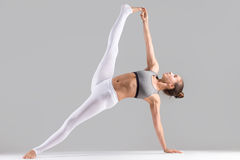 Young woman in Full Version of Vasisthasana pose, grey studio royalty free stock photography