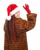 Young woman in fur and christmas hat waving hello Stock Image
