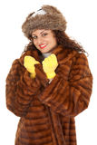 Young woman in a fur coat. Beautiful young woman in a fur coat, hat and yellow mittens Royalty Free Stock Photo
