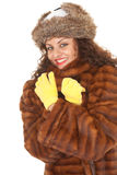 Young woman in a fur coat. Beautiful young woman in a fur coat, hat and yellow mittens Royalty Free Stock Photography