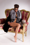 Young Woman In Fur Coat And Cat On Armchair Royalty Free Stock Images