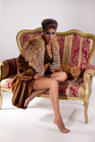 Young Woman In Fur Coat And Cat On Armchair Stock Images