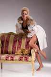 Young Woman In Fur Coat And Cat On Armchair Royalty Free Stock Photography