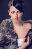 Young woman in a fur coat in earrings Royalty Free Stock Photos