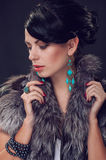 Young woman in a fur coat in earrings Stock Images