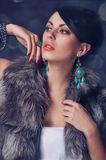 Young woman in a fur coat in earrings Royalty Free Stock Image
