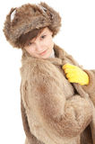 Young woman in a fur coat and hat. Beautiful young woman in a fur coat, hat and yellow mittens Royalty Free Stock Images