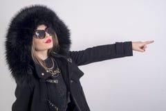 Young woman with fur coat. Young woman with fur hat, black sunglacess and redlips Stock Photo
