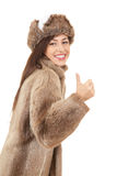 Young woman in fur coat and hat with thumb up Stock Photography