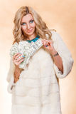 Young woman in a fur coat holding money Royalty Free Stock Photo