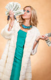 Young woman in a fur coat holding money Stock Photo