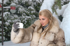The young woman in a fur coat stands in the snow-covered park Sh Royalty Free Stock Photos
