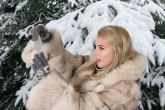 The young woman in a fur coat stands in the snow-covered park Sh Stock Photography