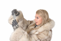 The young woman in a fur coat stands and takes photo  by phone a Stock Images
