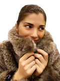 Young beautiful woman in fur coat. A young beautiful woman wearing a fur coat, with a smile on her face Stock Images