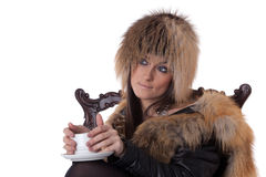 Young woman in fur with cup of coffee. Royalty Free Stock Photo