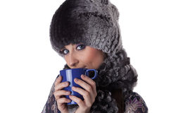 Young woman in fur with cup of tea. Royalty Free Stock Photography
