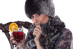 Young woman in fur with glass of mulled wine. Royalty Free Stock Image