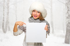 Young woman in fur hat with empty card at forest Stock Photo