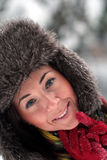 Young woman in fur hat face close up on the snow. Young smiling woman in a fur cap and red gloves on the snow Royalty Free Stock Image