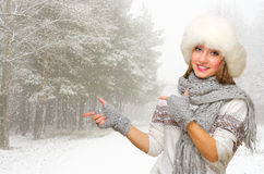 Young woman in fur hat shows pointing gesture at forest Royalty Free Stock Photography