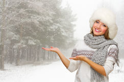 Young woman in fur hat shows welcome gesture at forest Stock Photo