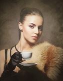 A young woman in fur holding a cup of coffee Royalty Free Stock Image