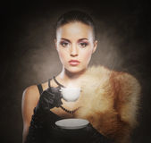 A young woman in fur holding a cup of coffee Royalty Free Stock Photo