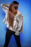 Young woman in fur long hair blue background Stock Photo