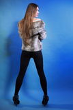 Young woman in fur long hair blue background Stock Images